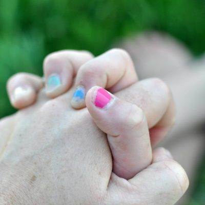 tween girl with hands folded with pink and blue nail polish by Katie M. Reid Photography