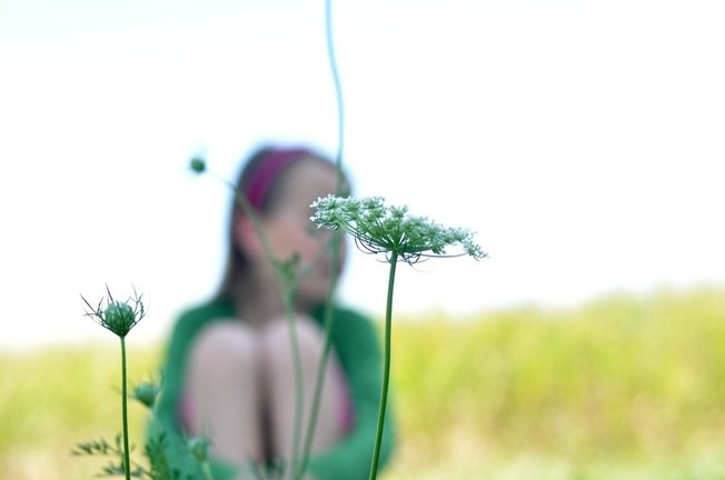 Tween girl in field and flower by Katie M. Reid Photogrpahy