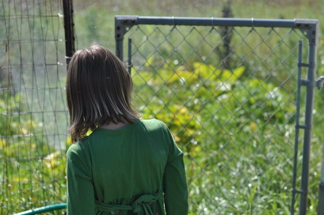 Girl walking through gate to garden by Katie M. Reid