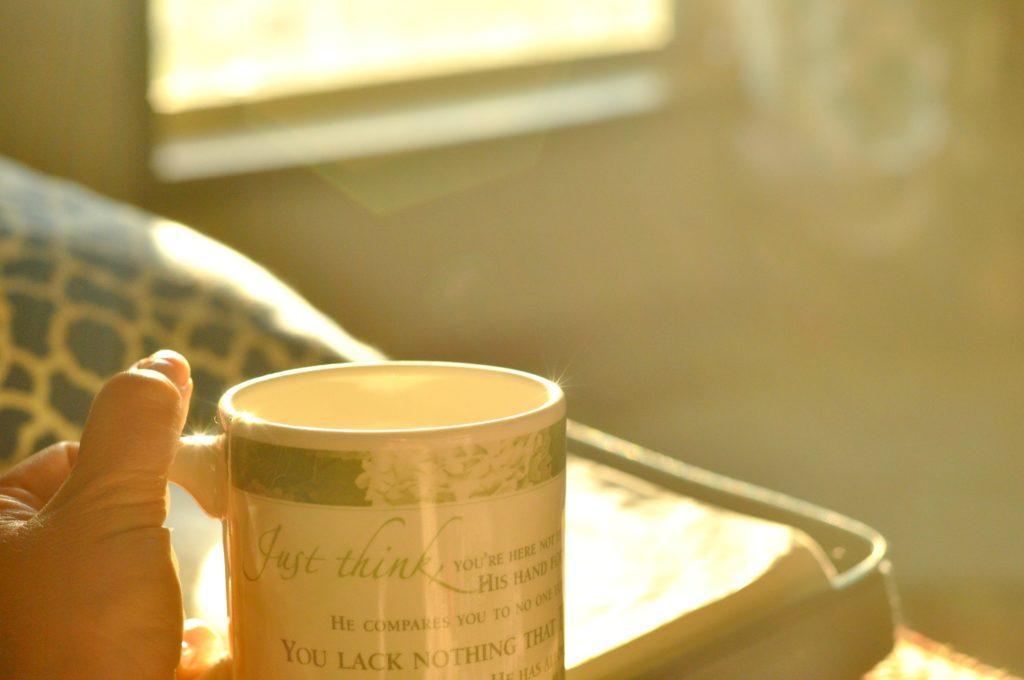Holding tea mug at sunrise by Katie M Reid Photography